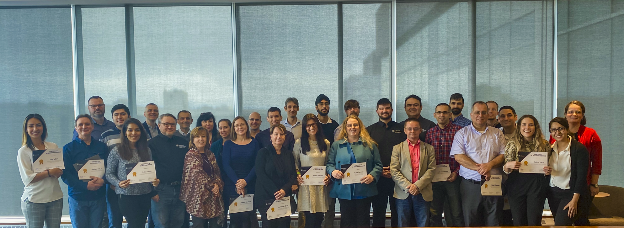 diverse group of professionals standing and holding certificates