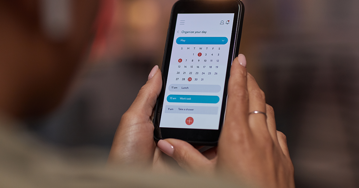 female hands holding smartphone with electronic calendar displayed
