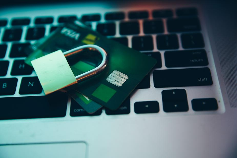 credit cards and a lock piled on top a laptop keyboard