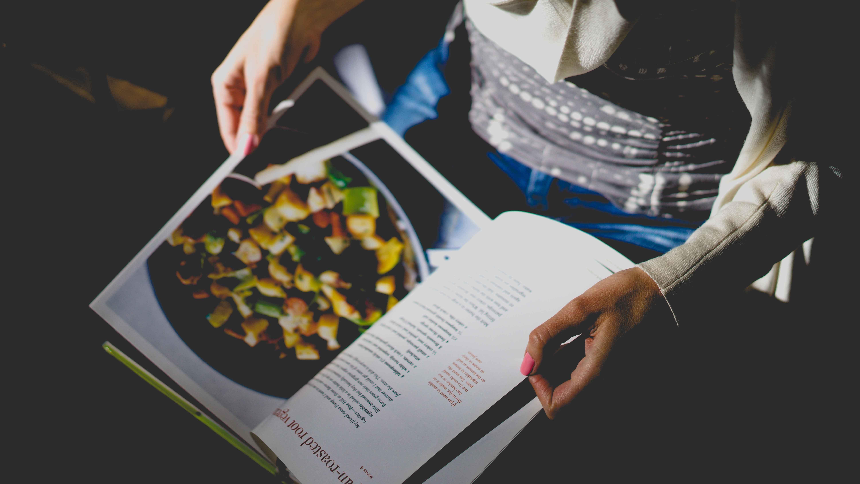 A cookbook is held open