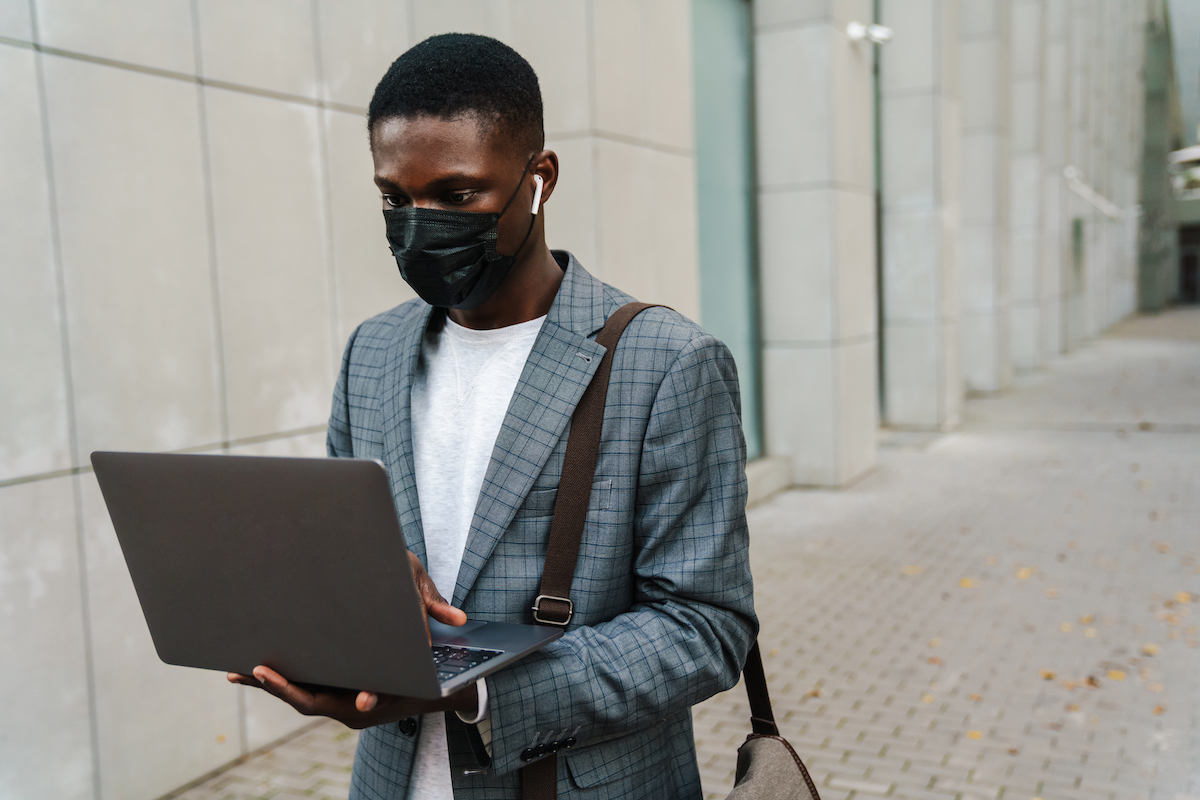 Young male wearing face mask while walking and looking at laptop screen