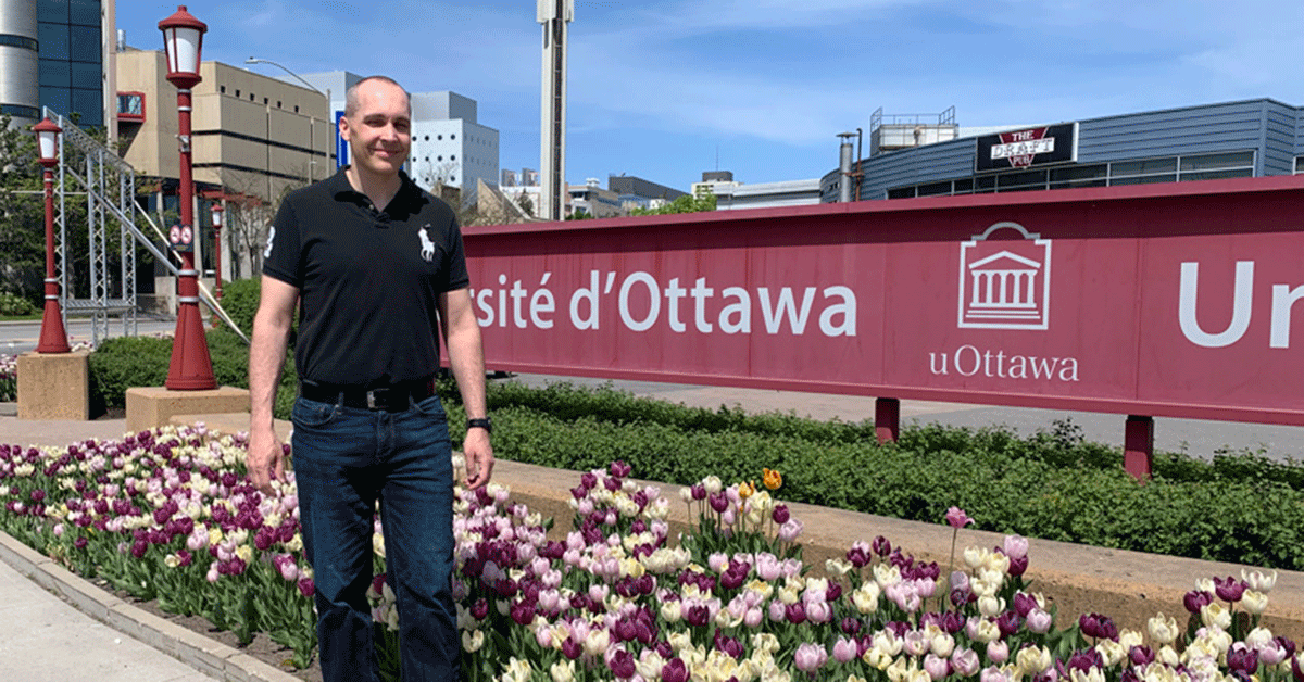 Nicolas Buache standing in from of University of Ottawa sign