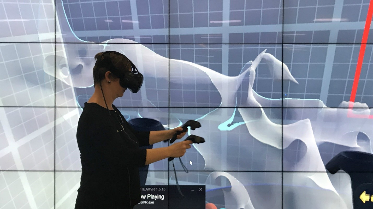 Woman in front of big screen with VR glasses and equipment