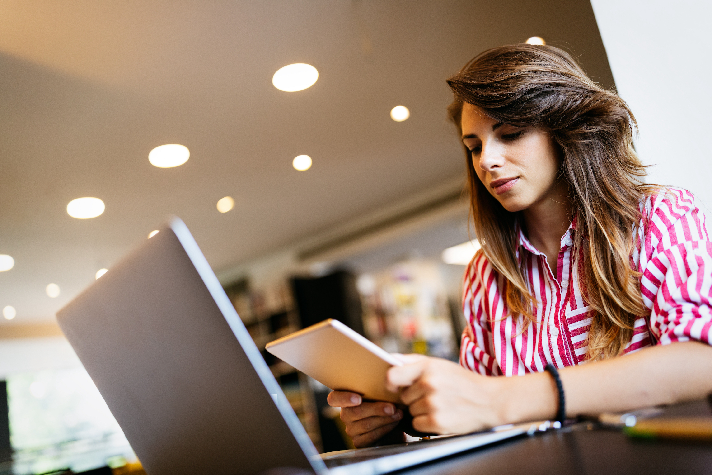 étudiante souriante qui travaille sur ordinateur portable et tenant une tablette